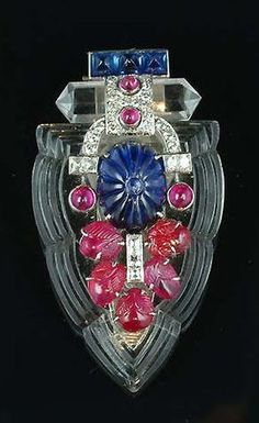 An Art Deco rock crystal, sapphire, ruby and diamond clip brooch, circa 1925, the shield-shaped rock crystal plaque decorated with a fluted sapphire, carved rubies and ruby cabochons, old brilliant and single-cut diamonds, capped by a faceted rock crystal and a three sugarloaf sapphires. #ArtDeco #clip #brooch