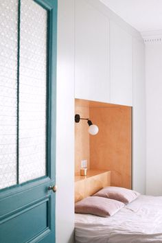 teal painted door with white walls in modern bedroom with built-in storage.