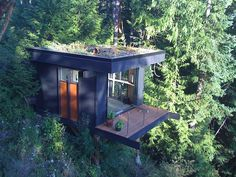 "Forest Home Office Cube, situated above Chuckanut Bay in Bellingham, Washington. ""I designed my office to be as unobtrusive as possible, to be an uncluttered work space, a guest house that keeps 'em coming back, and an inspired meditation room,"" says Frazier. ""It has a green roof so when we see the structure from the house it fits into the forest."""