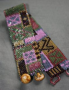 This bracelet measures 7 inches end to end, and almost 1 inch thick. This is a hand stitched peyote stitch bracelet, every bead is stitched on one by one, the design is random, unique, and a one of a kind with green, pink, garnet, grey, olive, and fuchsia patches! Dont pass this one up, you wont find one like it again! 2 glass button for clasps! To go to my shop click here http://www.etsy.com/shop/BeadSoupJewelry Save this for later by clicking on the heart