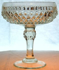 """Indiana Glass Company clear glass Diamond Point design Compote circa 1966.  This beautiful vintage Depression glass piece is made of thick clear glass with a cut diamond point design around the entire lower part of the bowl with a flat rim.  Has a diamond design accent on the stem.  In excellent condition.  Measures 7-1/4"""" tall and the bowl is approximately 2-1/2"""" deep and has a diameter of 6""""."""