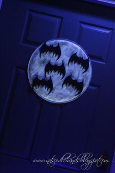 Glow-in-the-Dark moon with bats! Metal pizza pan, glow in the dark paint with round sponge to get a thin coat with texture similar to the moon!  And glitter bats!  Plus a black light bulb in the porch lamp!