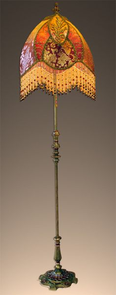 Elegant antique floor lamp with a gothic leaf style shade. Shade is a rich red with metallic gold accents. Gold lame, metalliclace and regal metallic damask make up the panels of the shade. Heavy gold metallic vetment appliques are applied in the leaf panels. This is a majestic lamp with hand beaded glass fringe in golds and reds.