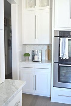 Modern White Kitchen w/ Coffee Bar and Herringbone Backsplash in white Carrara Marble + Marble Countertops