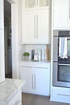 Modern White Kitchen w/ Coffee Bar and Herringbone Backsplash in white Carrara Marble + Marble Countertops