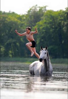 Summer fun with your horse! Horse swimming in creek being a diving board for his boy that is jumping off him into the water. They are having such fun and what a good horse just standing there like that. I miss the days of playing with my horse in the water!