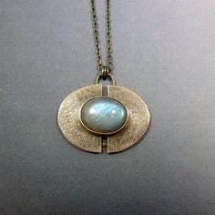 This listing is for an elegant, shimmering labradorite pendant. This piece of handmade gorgeousness features a delicious blue/grey labradorite cabochon absolutely choc-full of flash. This piece has a fantastic shimmering texture and I have created this by etching it and hand-engraving. The silver is also oxidised which gives it an aged look and adds depth to the texture. Heres the details:    ♦ ♢ Materials: Oxidised sterling silver, labradorite  ♦ ♢ Size: The stone is 14x10mm The pendant is…