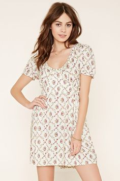 A woven babydoll dress by Motel™ with a lattice-like floral print, a scoop neckline, short sleeves, ruffled trim, a subtly shirred waist, and a concealed back zipper. .