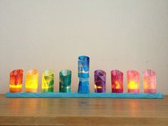 For 3rd grade tinker style menorah:  Cut plastic water bottles, cover in colored tissue, battery powered tea light inside