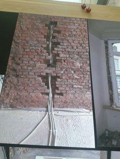 Wegwerken van leidingen in ruwe bakstenen muur.