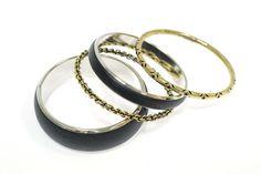 Juego de 4 pulseras rígidas. Forma de aro. Color negro y dorado envejecido. Diferentes acabados y grosores.    Medidas diámetro 6 cm aprox.  Ref.: AG8190N  http://www.meigallo.com/articulo/728/juego-de-4-pulseras-rigidas