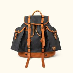 Crafted of waxed canvas and leather with a distressed vintage finish, this men's vintage military rucksack / backpack was built to honor the memory of good men and good days. Also available in tan (shown here in navy charcoal). Rucksack Backpack, Canvas Backpack, Waxed Canvas Bag, Canvas Bags, Tan Leather, Leather Bags, Leather Backpacks, Rugged Men, Best Gifts For Men