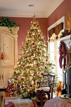 Don't skimp on the lights on your tree. This tree glows with white candles and burgundy and gold ornaments against the soft red of the family room walls. A Christmas pillow on a fireside chair, and even the gift wrap, all echo the festive color palette.