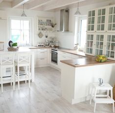 Kitchen. Grey floor, wood countertop, white cabinets
