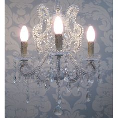 A delicate 3-arm crystal chandelier with glass drops and cups, and elegant rococo beaded necklace arms.