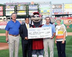 """Univest Bank and Trust Co. Executive Vice President David Kepler, left, and Univest Corporate Banking President Philip Jackson, joined by IronPigs mascot FeFe, present Wildlands Conservancy President Chris Kocher and board Chairman Jane Ervin with a $2,500 donation. Univest Bank and Trust Co. recently presented the Wildlands Conservancy with a check for $2,500 earned through the Lehigh Valley IronPigs """"Double Plays Pay"""" sponsorship."""