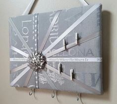 This decorative memo board in designer European-themed gray fabric is accented with various ribbons and satin flower in the center. It can be used as a photo/memo board to display your notes, mementos and photos, hair bows etc. Hooks attached to the bottom can hold keys, jewelry and much more. One of the ribbons reads Home Is Where The Heart Is. Four micro pegs included. Size: 10in wide x 8in tall. This board is in stock and ready for shipping. My memo boards and fabric pictures are ca...