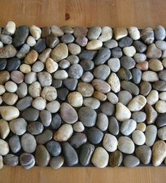DIY Pebble Bath Mat - you need: ◾1 rubber Welcome mat ◾4 bags of river rocks ◾some contact adhesive  All from the Dollar store.