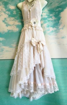 One of a kind.  The top of this dress is tea stained cotton crochet with applique and tie halter straps. The top layer of the skirt is gold flecked tulle with hi low ruffled hem and backed in light weight cream colored satin. Satin bow detail on front. The underskirt is pale blush tiered cotton with satin trim and lace hem. Cream lace waist band with soft white lace sash. Size medium. Measurements Bust 34-36 Waist 28-32 Hip 36-38 Length 51-62