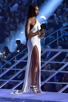 Naomi Campbell presenting at the VMAs in a white column dress with one shoulder and thigh-high slit by Brandon Maxwell.