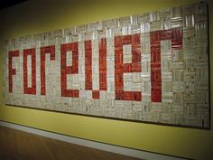 "This Sept. 27, 2014 photo shows a solid wall of 4,000 paperback romance novels spelling out the word ""FOREVER"" in an art installation at Crystal Bridges Museum of American Art in Bentonville, Ark. The work by John Salvest was part of a major contemporary art show at the museum in late 2013. Salvest said there was an ""underlying sadness"" to collecting the discarded books from thrift shops in an era when fewer people read physical books. (AP Photo/Beth J. Harpaz)"