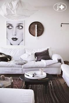 On aime: le tapis tissé et le contraste des coussins et cadres dans des coloris plus foncés.