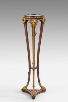 "A well modelled and carved mahogany and gilt wood Torchere of Robert Adam design, the supports with continuous oak leaf carving, the tops with stylised rams-heads, original gilding now patinated to a bronze color Ca1890 England. 44.25""H x 14""W x 14""D."
