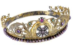 A multi gem-set tiara  Of scrolling openwork design, composed of highly stylised repoussé acanthus leaves and floral motifs, decorated with cabochon amethysts and emeralds, the centre set with a rose-cut diamond and garnet cross and a synthetic ruby and paste cluster, on a band of stained freshwater cultured pearls, all gemstones in foiled closed-back settings, mounted in silver gilt, composite, height at tallest point approx. 8.5cm (illustrated inside the front cover)