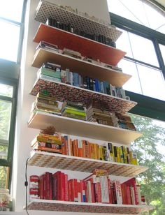 DIY Bookshelves!  Line the bottom of each shelf with left over wallpaper scraps. Such a great idea, especially for a loft area, where shelves can extend high above eye level!