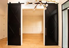 Large Black Barn Doors leading into an office off the main entrance with a panel feature wall, adding the perfect contrast to the light natural wood floors Custom Interior Doors, Front Hallway, Natural Wood Flooring, Black Barn, Main Entrance, Contemporary, Modern, Barn Doors, Large Black