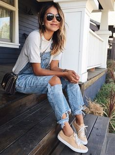 Trendy distressed denim overalls with simple white tee and comfy sneakers.