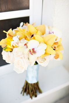 Yellow and white orchids with pale pink roses bridal bouquet.