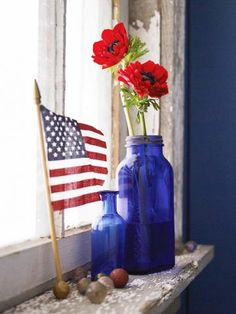 Sweet and simple window display of a miniature American flag, blue vases with red poppies, and marbles