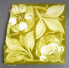 """Maw and Co hand painted dust pressed tile with a design of a stylised flower and scrolling stem with leaves, shades of green, 6"""" square, c1900. Probably designed by C H Temple."""