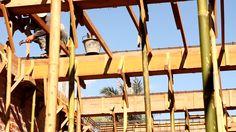Men prepare wooden beam box for second floor beam construction, construction site, Laos