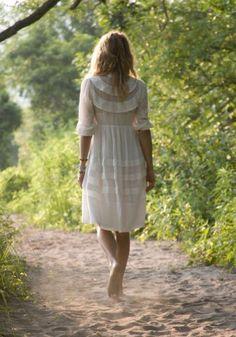 A woman in a white dress walks along a sandy road.