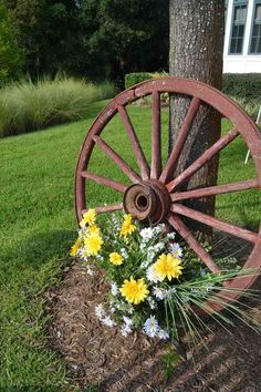 Holzrad und Blumen als Deko im Vorgarten