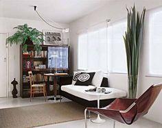 Compacto, este estar é formado basicamente de uma cadeira e um sofá de um só braço, pouco volumoso. A mesa de centro Tulipa, de desenho leve, serve como apoio. Um canto de leitura, com estante e mesa, complementa o espaço, tornando-o multiúso. Projeto de Heloisa Maia Campos.