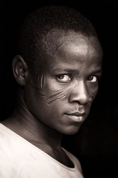 "Africa | ""An intense encounter at Nadoba"". Young Tamberma man from Togo with heavy facial scars and an intense look.  