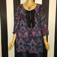 Kensie Purple and Blue Tumic This gorgeous tunic has a paisley print with various shades of purple and blue. The top of the tunic has black ribbon running down the front with six black buttons and a satin tie that has tassels. The top has a black lining. Tunic is 100% polyester Kensie Tops Tunics
