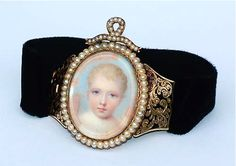 Gold bracelet, circa 1840, the articulated shoulders of which are decoratively enamelled in black. The bracelet contains a beautifully executed watercolour miniature of a child with blue eyes in dawn clouds, under crystal and within a pearl surround, the whole symbolic of mourning.