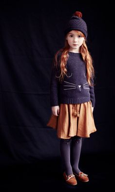 Little girl dressed in cute fall autumn outfit in black and burnt orange