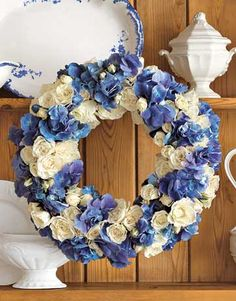 White spray roses and blue hydrangea florets are combined to wonderful effect. Get instructions and watch a behind-the-scenes video on how to make this beautiful wreath.   - CountryLiving.com