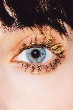 try dusting loose gold pigment (like MAC Old Gold Pigment) and a mixing base (like MAC's Medium Base) on top of mascara and combing through. This is a more extreme, glittery-doll lash look