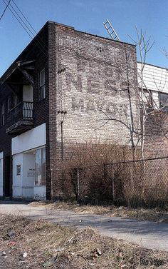 """""""Eliot Ness for Mayor"""" from his unsuccessful 1947 campaign for Mayor of Cleveland. Ness died at age 54 and was buried in Cleveland. This photo was taken in 1984; the building is now gone and this fragment of history with it. photo Thom Sheridan"""