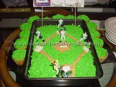 baseball birthday cake - giant chocolate chip cookie, dyed coconut. Cupcakes will have white icing w/ red stitching (not the green coconut)