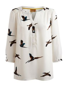 Joules Womens Half Buttoned Blouse, Creme Pheasant.                     If you're looking for a wear-anywhere blouse that works well with everything from skirts and trousers to jeans then look no further than this soft feel top. Featuring our much-loved flying pheasant print.  With an open neckline, rouched shoulders, half button placket and three quarter sleeves it drapes beautifully to achieve a flattering shape.