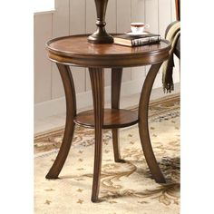 This beautiful round accent table features an inlaid parquet table top designed with bamboo and walnut veneers. A small circular shelf adds additional detail while also providing a small space for accents and extra decor in your home.