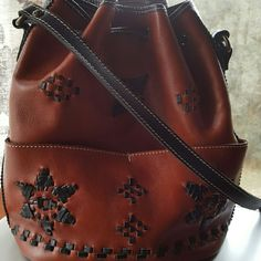 Patricia Nash Aztec bucket bag Beautiful soft creamy redish tan leather with black accents. Strap is in pristine condition. Bag  strap is extremely long so I added some extra holes to be able to reach it in arms length while wearing it. Doesn't take away from bag and it's was measured out to aline perfectly,Interior clean and exterior clean. No trades. Fabulous Condition . Please see all photos. No returns. Purchased from Macy's this season. Has pockets interior and exterior Price firm…