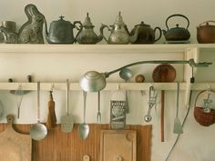 Frequently used kitchen items such as teapots, cooking utensils and cutting boards have a visual impact when arranged together on open shelves.